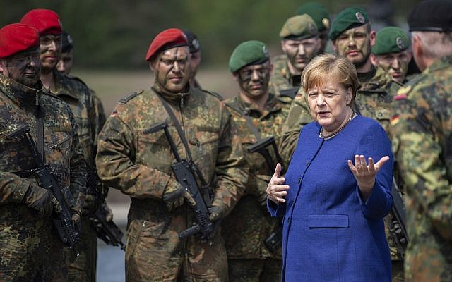 German Chancellor Angela Merkel, right, talks to soldiers of the Very High Readiness Joint Task Force (VJTF) after an exercise in Munster, Germany, May 20, 2019. In 2019 Germany will be in charge for the NATO Very High Readiness Joint Task Force. (Christophe Gateau/dpa via AP)