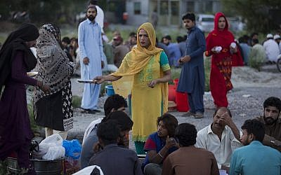 A transgender Pakistani provides food to people during the Muslims' fasting month of Ramadan in Islamabad, Pakistan, Monday, May 27, 2019. (AP Photo/B.K. Bangash)