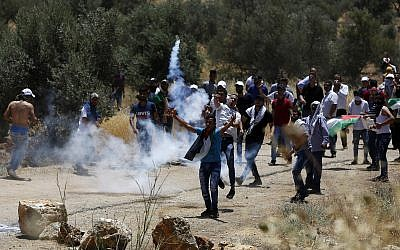 Illustrative -- Palestinian protesters throw back a tear gas canister fired by Israeli troops during a protest near the West Bank city of Nablus, June 28, 2019 (AP Photo/Majdi Mohammed)