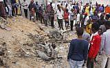 Illustrative: Somali people gather near destroyed buildings after a car bomb detonated in Mogadishu, Somalia, July 8, 2019. (AP Photo / Farah Abdi Warsameh)