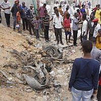 Illustrative: Somali people gather near destroyed buildings after a car bomb detonated in Mogadishu, Somalia, July 8, 2019. (AP Photo / Farah Abdi Warsameh)