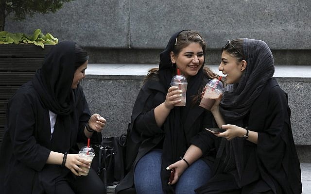In this Tuesday, July 2, 2019 photo, youngsters spend an afternoon while siting on steps outside a shopping mall in northern Tehran, Iran (AP Photo/Vahid Salemi)