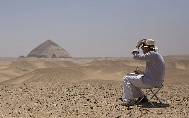 A member of an international delegation sketches the site of the Bent Pyramid during an event opening the pyramid and its satellites for visitors in Dashur, Egypt, Saturday, July 13, 2019 (AP Photo/Maya Alleruzzo)