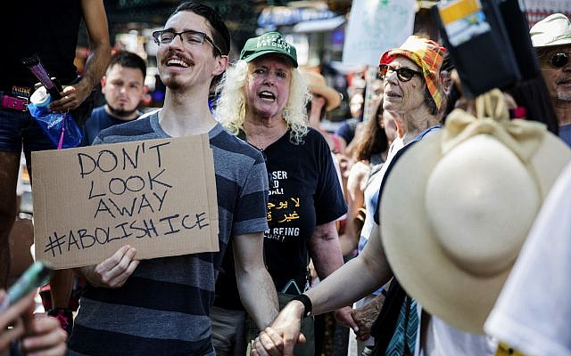 People holds hands as they chant at a rally before the start of a march in opposition to the Trump administration's plans to continue with raids to catch immigrants in the country illegally, July 14, 2019, in the Queens borough of New York. (AP Photo/Julius Constantine Motal)