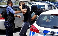 Two of the 12 Israelis suspected of gang raping a British tourist cover their faces with their shirts as they arrive at the Famagusta courthouse in Paralamni town, Cyprus, on July 18, 2019. (AP Photo/Petros Karadjias)