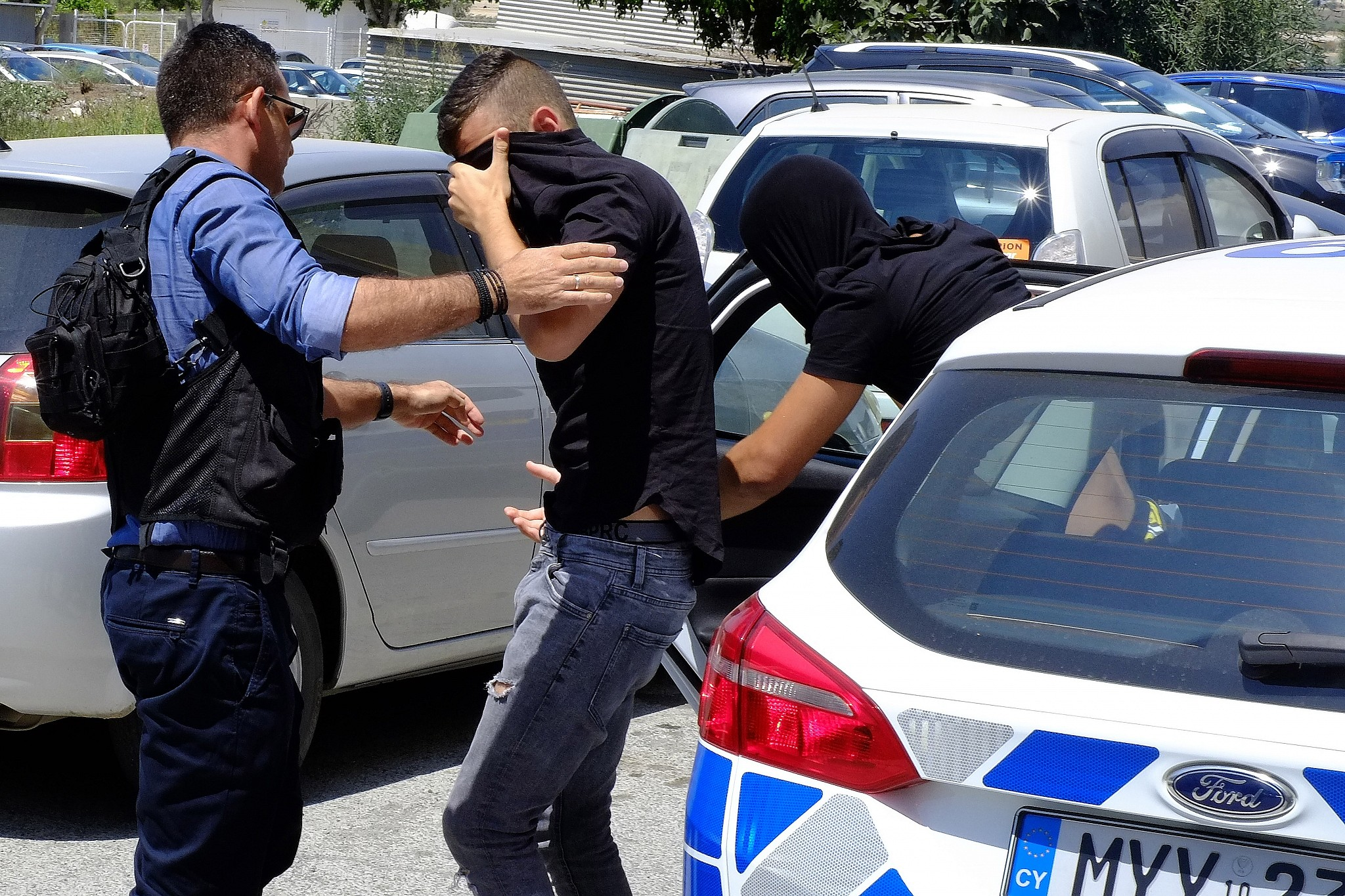 Two of the 12 Israelis suspected of gang raping a British tourist cover their faces with their shirts as they arrive at the Famagusta courthouse in Paralamni town Cyprus