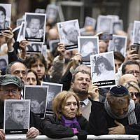 People hold up pictures of people who died during the bombing at the AMIA Jewish center that killed 85 people, on the 25th anniversary of the attack in Buenos Aires, Argentina, July 18, 2019. (AP Photo/Natacha Pisarenko)