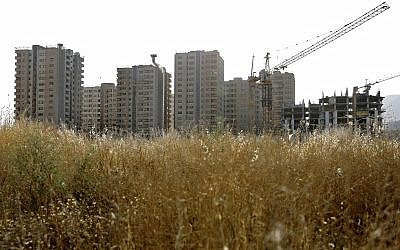 This July 6, 2019, photo shows residential towers in District 22 that consists of apartment high-rises and shopping malls arranged around an artificial lake called Chitgar, under construction on the northwestern edge of Tehran, Iran (AP Photo/Ebrahim Noroozi)