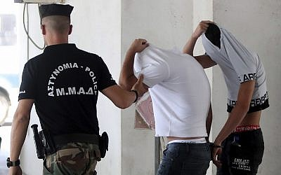 Israeli suspects cover their faces with their shirts as they arrive at the Famagusta courthouse in Paralamni, Cyprus, July 26, 2019 (AP Photo/Petros Karadjias)