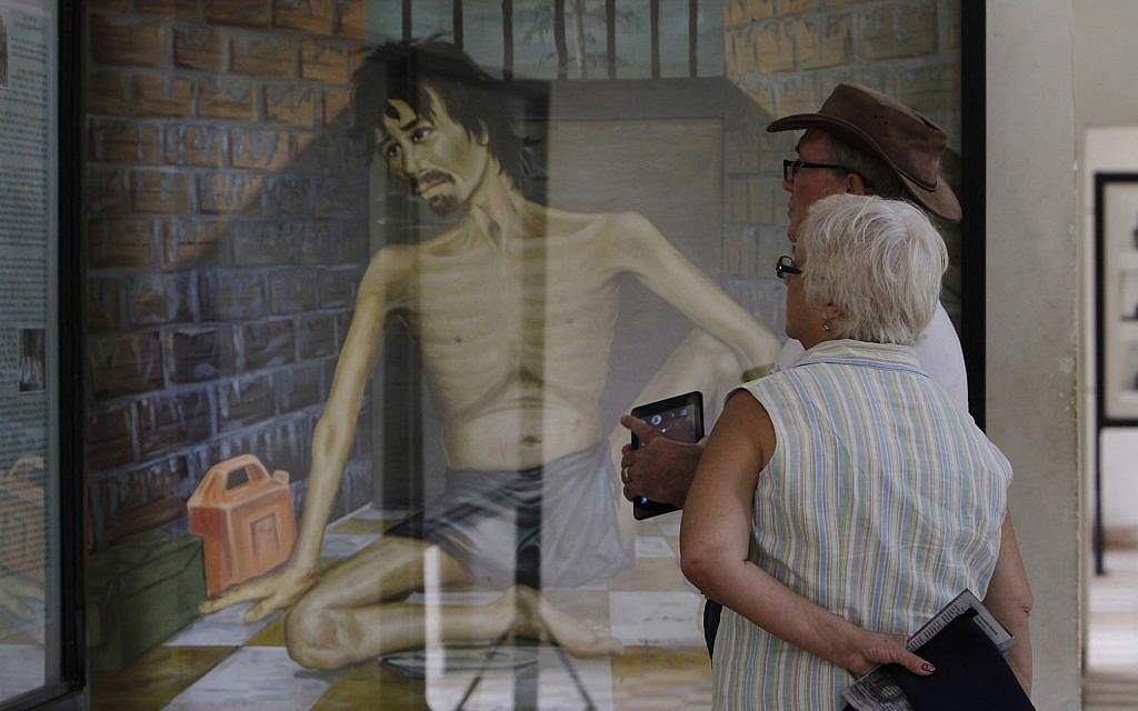 Illustrative: In this July 10, 2014 photo, tourists look at a painting depicting Khmer Rouge torture at the Tuol Sleng Genocide Museum, formerly the most notorious Khmer Rouge prison, in Phnom Penh, Cambodia. (AP Photo/Heng Sinith)