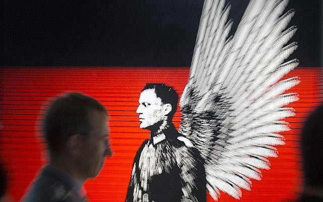 In this zoomed picture an officer of the German Federal Armed Forces, Bundeswehr,  stands in front of the serigraphy 'Hero portrait. Claus Schenk Graf von Stauffenberg' (2004) by German artist  Petrus Wandrey during the press preview of the new special exhibition 'Attentat auf Hitler. Stauffenberg und mehr' (Assassination attempt against Hitler. Stauffenberg and more) in the Military History Museum in Dresden, Germany, Wednesday, July 2, 2014. (AP Photo/Jens Meyer)