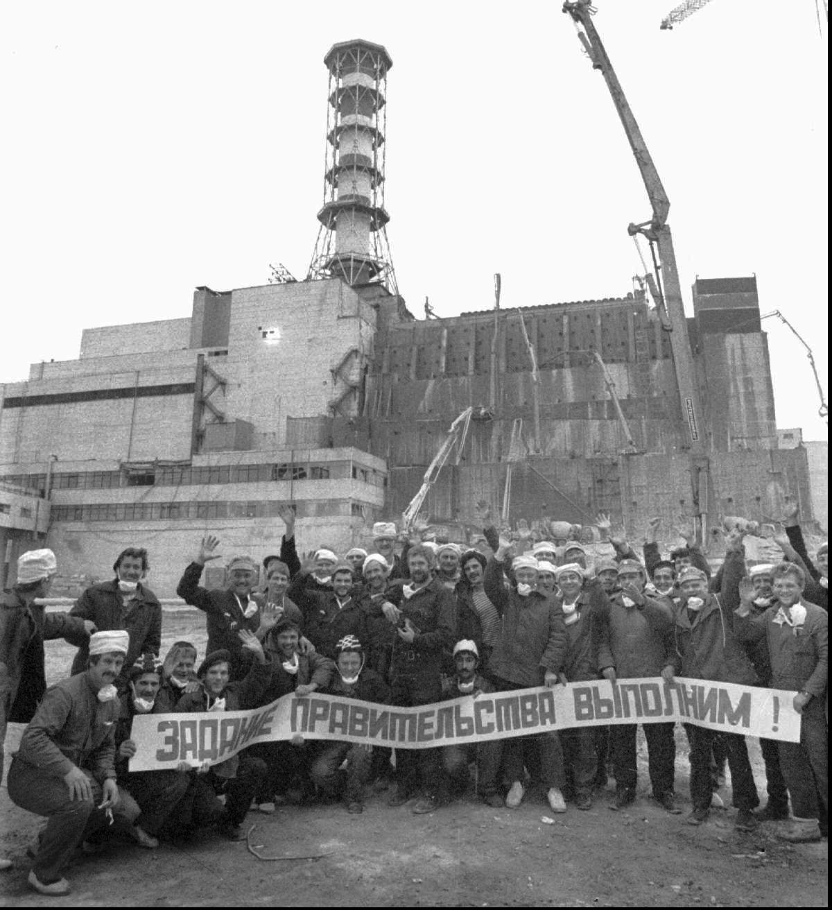 """Workers who constructed the base for a cement sarcophagus to cover Chernobyl's exploded Reactor 4 pose, in front of the still-exposed destroyed reactor building, with a poster reading: """"We carried out the mission ordered by the government"""". (AP Photo/ Volodymyr Repik)"""