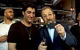 Screen capture from video of Israel Democratic Party leader Ehud Barak, right, demonstrating how to use a credit card. (Twitter)