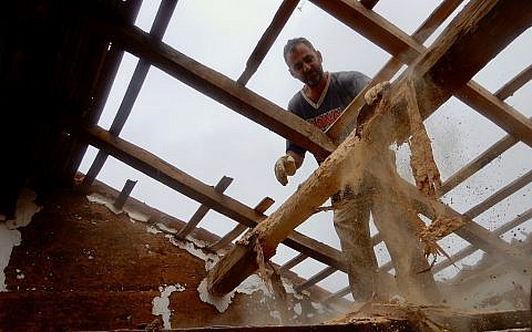 Tamir Burstein Nevo removing the the termite-ravaged roof of a traditional Portuguese farmhouse in southern Portugal on May 9, 2019. (Melanie Lidman/Times of Israel)