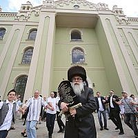Yaakov Dov Bleich carrying a Torah scroll into the synagogue of Drohobycz, Ukraine on July 3, 2019. (Rephael Isaak Vilenskiy via JTA)