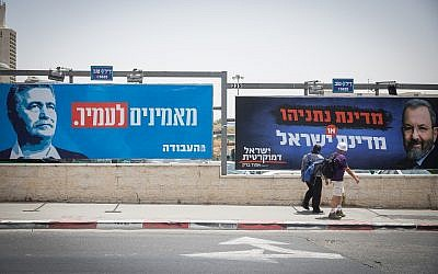 People walk near election campaign posters showing Labor party leader Amir Peretz, left, and Ehud Barak, right, at the entrance of Jerusalem on July 17, 2019. (Noam Revkin Fenton/Flash90)