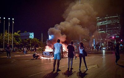 A car is seen on fire after its driver was attacked during a protest following the death of 19-year-old Ethiopian, Solomon Tekah who was shot and killed few days ago in Kiryat Haim by an off-duty police officer, in Tel Aviv, July 2, 2019. (Adam Shuldman/Flash90)