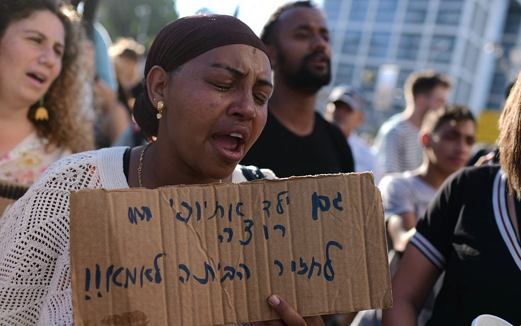 "Ethiopian-Israelis and supporters take part in a protest against police violence and discrimination following the death of 19-year-old Solomon Tekah, who was shot and killed on June 30 by an off-duty police officer, in Tel Aviv, July 3, 2019. The sign reads, ""An Ethiopian child also wants to get home to mother."" (Tomer Neuberg/Flash90)"