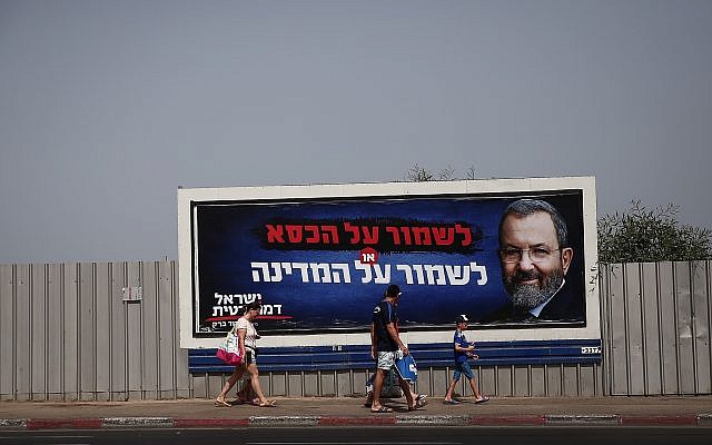 People walk next to election poster for Ehud Barak, head of the Israel Democratic Party, in Tel Aviv, July 17, 2019. (Miriam Alster/Flash90)