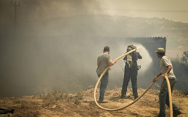 Volunteers try to extinguish a fire in the West Bank settlement of Shavei Shomron, July 17, 2019. (Sraya Diamant/Flash90)