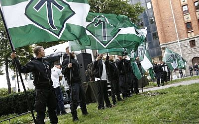 Illustrative: Supporters of the neo-Nazi Nordic Resistance Movement hold flags during a demonstration at the Kungsholmstorg square in Stockholm, Sweden on August 25, 2018. (Fredrik Persson/Getty Images/AFP)