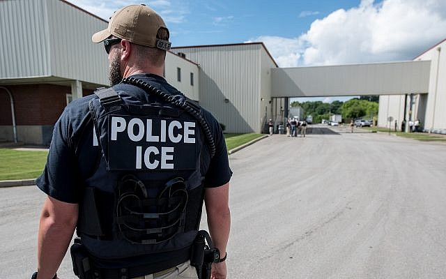 An Immigration and Customs Enforcement special agent prepares to arrest alleged undocumented immigrants in Salem, Mass., June 19, 2018. (Smith Collection/Gado/Getty Images via JTA)
