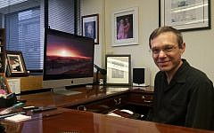 Prof. Avi Loeb in his Harvard office. His computer wallpaper features a photo of Proxima Centauri, the closest known star to our Sun. (Rich Tenorio/Times of Israel)