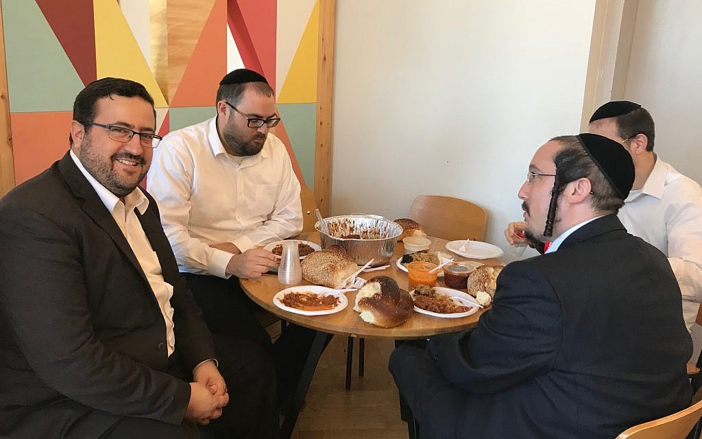 KamaTech's Moshe Friedman, left, partaking in happy hour at the Ampersand Haredi co-working space in Bnei Brak, July 4, 2019 (Shoshanna Solomon/Times of Israel)