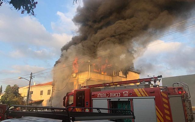 Firefighters work to extinguish a blaze at the home of Carmel Mauda in the central city of Rosh Ha'ayin on July 6, 2019. (Israel Police)