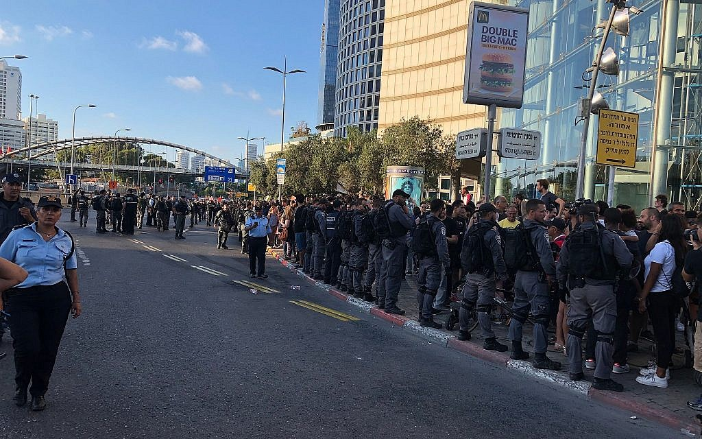 Police officers form a line to prevent protesters from rushing into the street at Hashalom interchange in central Tel Aviv amid a protest by the Ethiopian-Israeli community, July 3, 2019. (Naomi Lanzkron)