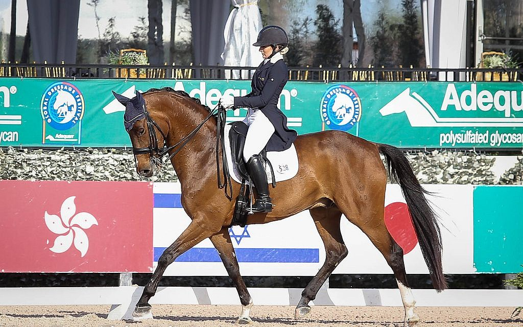 US-Israeli dressage rider Micah Deligdish riding in front of an Israeli flag. (Annan Hepner Santos)