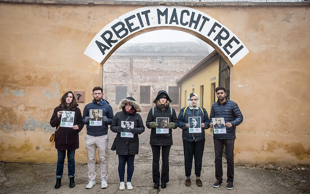 Trip leader Elan Kawesch (second from left) and participants with photographs of victims inside the 'Small Fortress' of Terezin, in Czech Republic, February 2019 (Matt Lebovic/The Times of Israel)