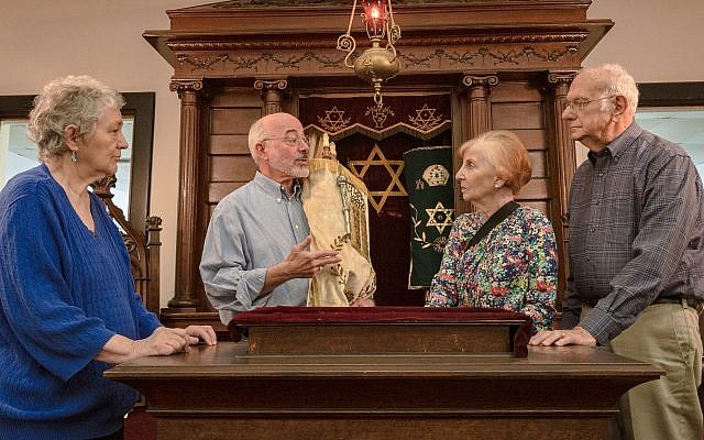 The members of Temple Mishkan Israel — from left, Hanna Berger, Ronnie Leet, Joanie Gibian Looney and Charles Pollack — stand in front of the Torah ark. The synagogue has not held weekly services for decades. (Amy Milligan via JTA)
