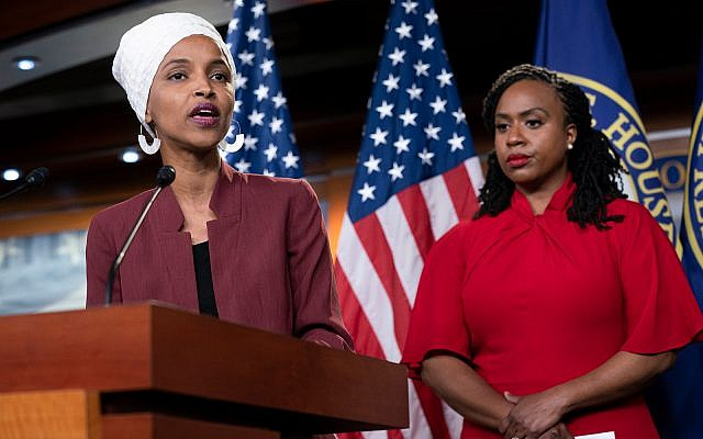 """US Rep. Ilhan Omar, D-Minn., left, joined at right by US Rep. Ayanna Pressley, D-Mass., responds to remarks by President Donald Trump after he called for four Democratic congresswomen of color to go back to their """"broken"""" countries, July 15, 2019. (AP Photo/J. Scott Applewhite)"""