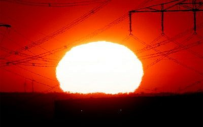 The sun rises near power lines in Frankfurt, Germany, as a heat wave scorches Europe, July 24, 2019. (AP Photo/Michael Probst)