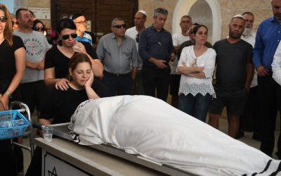 Dikla Hasdai mourns near the body of her husband, Ofir Hasdai ,who was shot dead at a parking lot in Ramle, during his funeral at the Ramle cemetery on July 29, 2019. (Avi Dishi/Flash90)