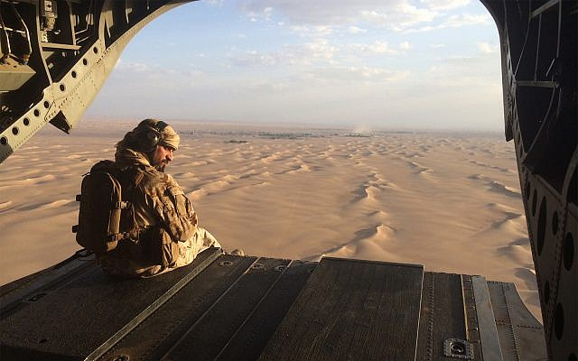 An Emirati gunner watches for enemy fire from the rear gate of a United Arab Emirates Chinook military helicopter flying over Yemen, September 17, 2015. (AP Photo/Adam Schreck, File)