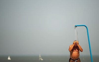 A man cools off in a beach shower during a hot summer day at the beach in De Haan, Belgium, July 25, 2019. (AP Photo/Francisco Seco)