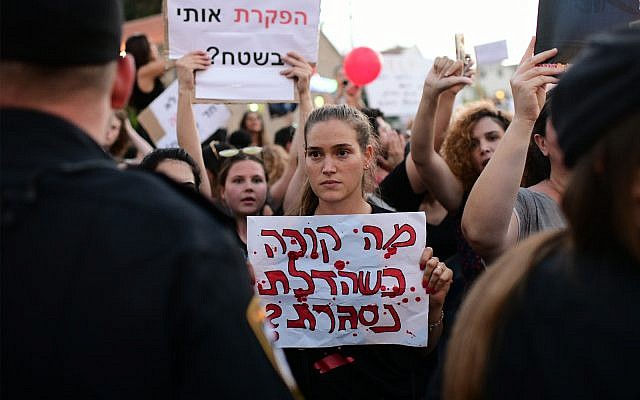 """Parents protest in Tel Aviv against the abuse of children and infants in kindergartens in Israel, July 7, 2019. The sign reads """"What happens when the door closes?"""" (Tomer Neuberg/ Flash90)"""