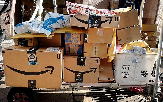 Amazon Prime boxes are loaded on a cart for delivery, October 10, 2018 in New York. (AP Photo/Mark Lennihan)