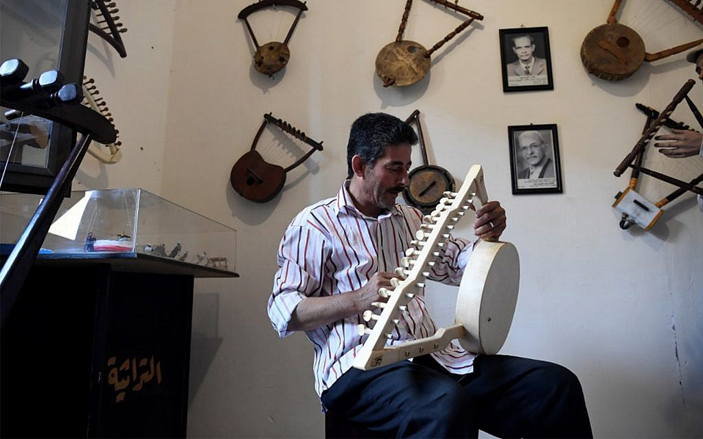 Egyptian craftsman Mohamed Ghaly adds the finishing touches on a semsemia that he made at the Canal 20 cultural museum in the northeastern city of Port Said at the northern terminus of the Suez Canal, on May 29, 2019. (Khaled Desouki/AFP)