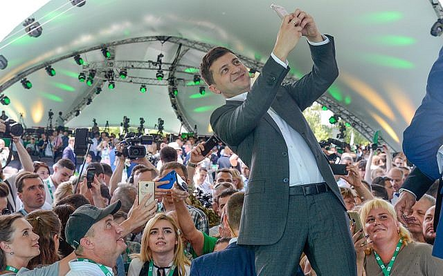 Ukrainian President Volodymyr Zelensky takes a selfie at the first congress of his party called Servant of the People in the city Botanical Garden, Kiev, Ukraine, June 9, 2019. (AP Photo/Zoya Shu)