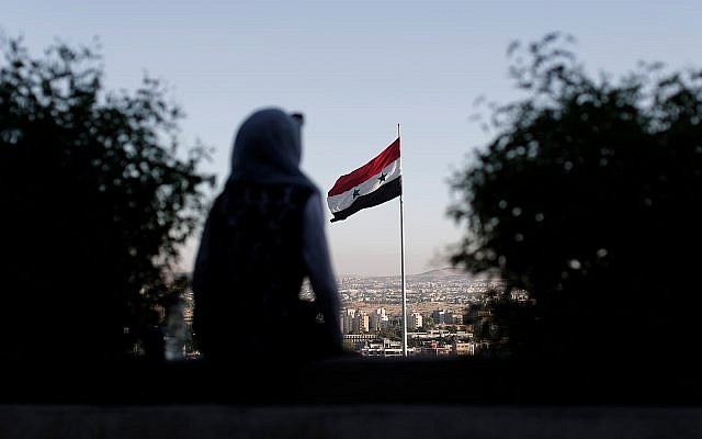 Illustrative: a woman overlooking the Syrian capital Damascus, July 24, 2019. (AP Photo/Hassan Ammar)