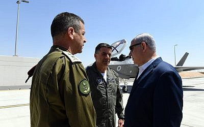 Prime Minister Benjamin Netanyahu, right, IDF Chief of Staff Lt. Gen. Aviv Kohavi, left, and Air Force chief Maj. Gen. Amikam Norkin, center, at the Nevatim Air Force Base on July 9, 2019. (Ariel Hermoni/Defense Ministry)
