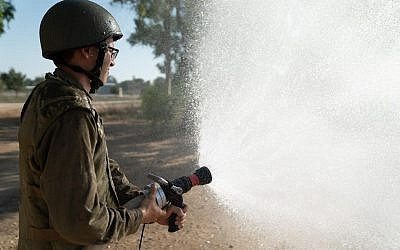 An Israeli soldier uses a fire hose in an undated photograph. (Israel Defense Forces)