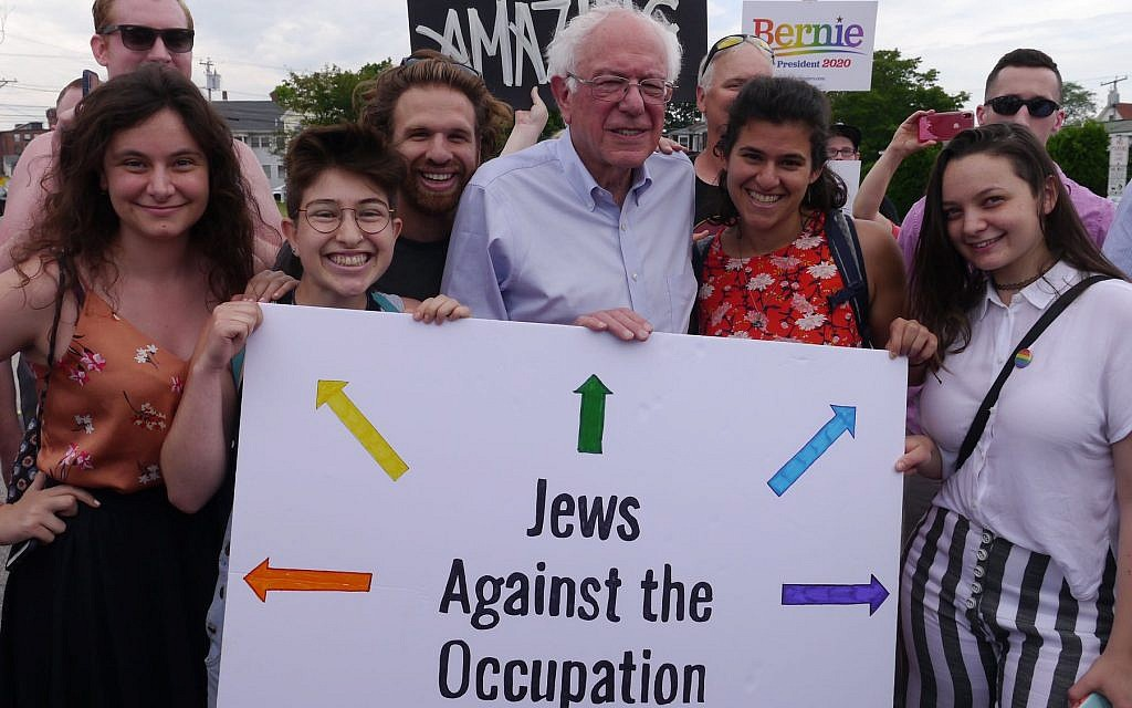 "Vermont Senator Bernie Sanders poses with IfNotNow activists in New Hampshire, including University of Michigan student Becca Lubow on the far left, and holds a sign that reads ""Jews Against Occupation."" (Courtesy/IfNotNow)"