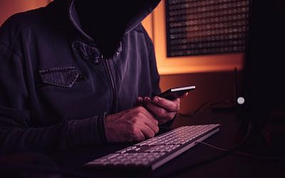 Illustrative image of a computer hacker using a smartphone (stevanovicigor; iStock by Getty Images)