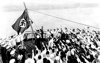 The raising of the new swastika flag aboard the S.S. Bremen as it was docked in the Hudson River. Captain Adolf Ahern, behind the stand with the draped Nazi flag, conducted the ceremonies. (Photo by Jimmy Condon/NY Daily News Archive via Getty Images)
