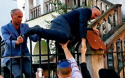 Chief Polish Rabbi Michael Schudrich climbs fence of barricaded Krakow synagogue. (Shimon Briman/JTA)