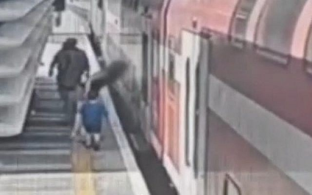 A mother tries desperately to get the train doors to open after leaving her baby momentarily on the train to help another child, at the Binyamina train station on July 11, 2019. (Channel 12 screen capture)